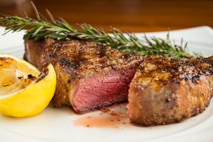 cooked steak with rosemary and lemon garnish